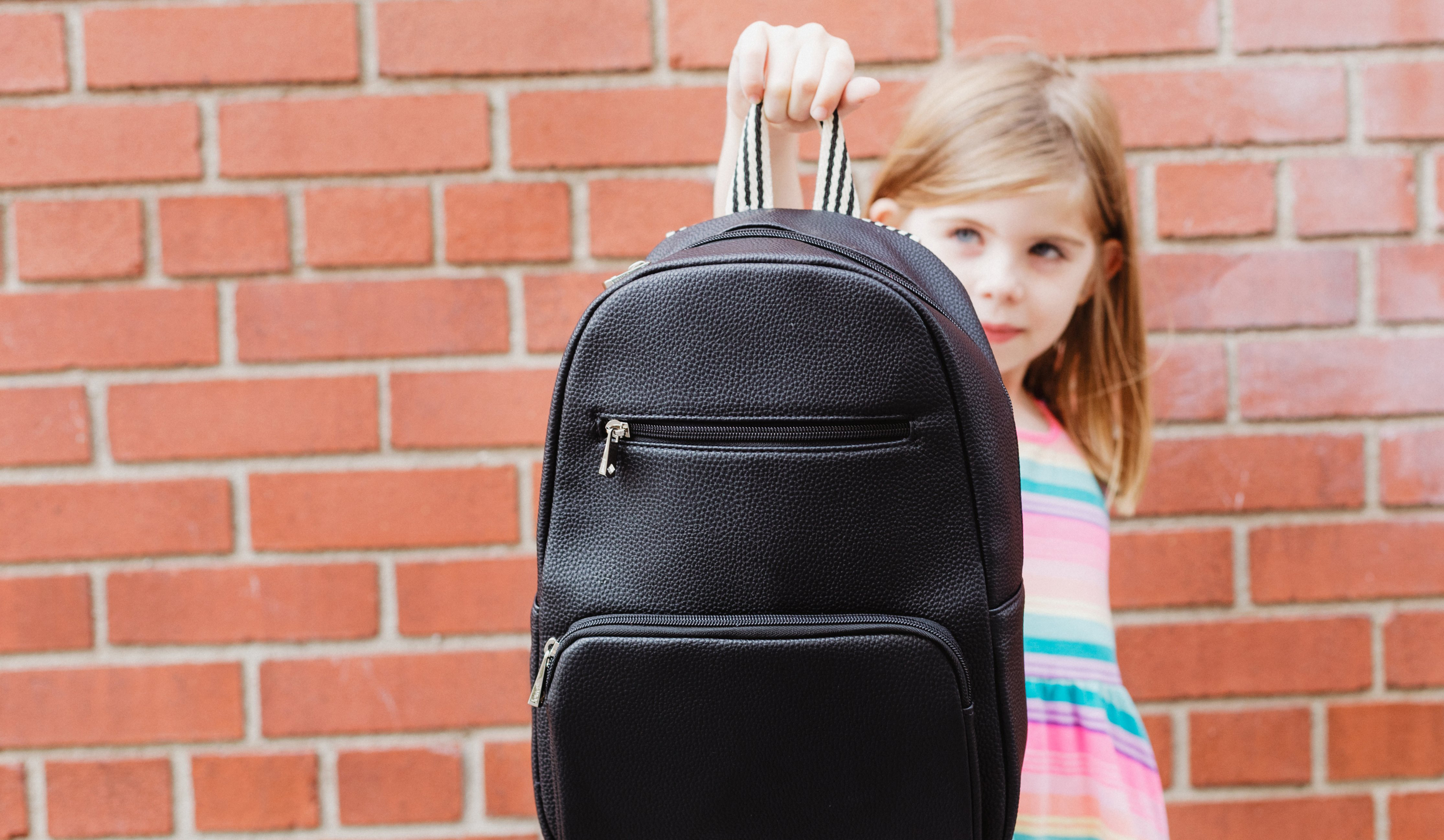 cropped_back-to-school-holding-out-backpack